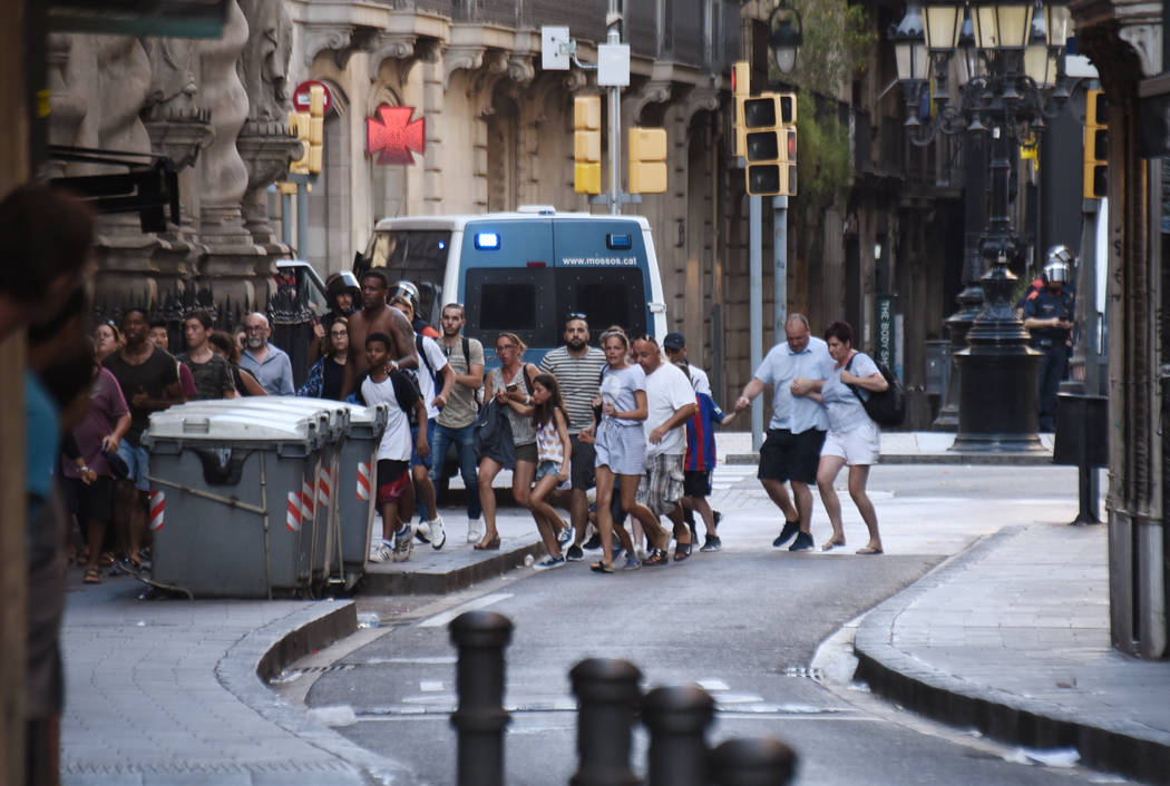 People flee from the scene after a white van jumped the sidewalk in the historic Las Ramblas district of Barcelona, Spain, crashing into a summer crowd of residents and tourists Thursday, Aug. 17, ...