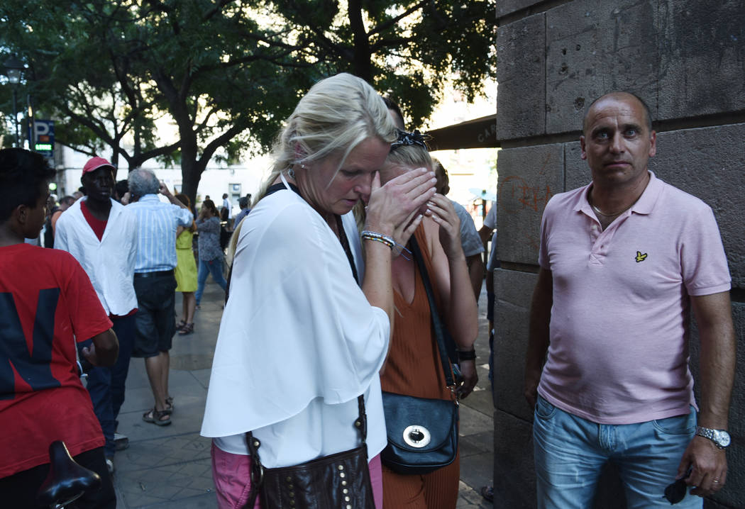 A woman is comforted as crowds flee from the scene after a white van jumped the sidewalk in the historic Las Ramblas district of Barcelona, Spain, crashing into a summer crowd of residents and tou ...
