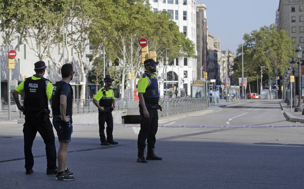 Police officers cordon off a street in Barcelona Thursday, Aug. 17, 2017. Police in the northern Spanish city of Barcelona say a white van has jumped the sidewalk in the city's historic Las Rambla ...