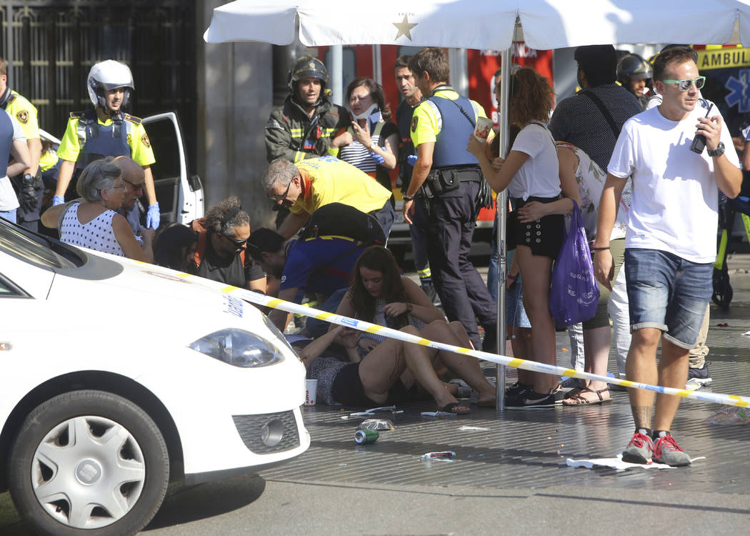 Injured people are treated in Barcelona, Spain, Thursday, Aug. 17, 2017 after a white van jumped the sidewalk in the historic Las Ramblas district, crashing into a summer crowd of residents and to ...