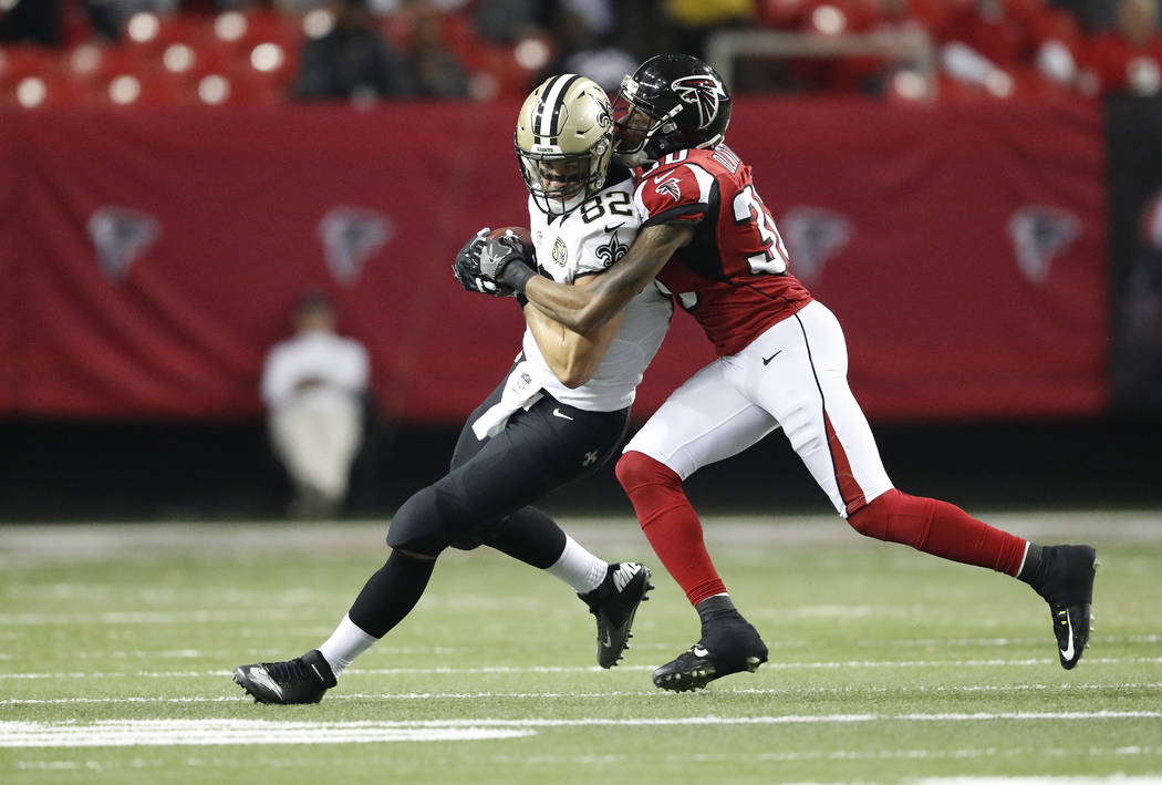 Atlanta Falcons cornerback Deji Olatoye (30) tackles New Orleans Saints tight end Coby Fleener (82) during the second half of an NFL football game, Sunday, Jan. 1, 2017, in Atlanta. (AP Photo/John ...