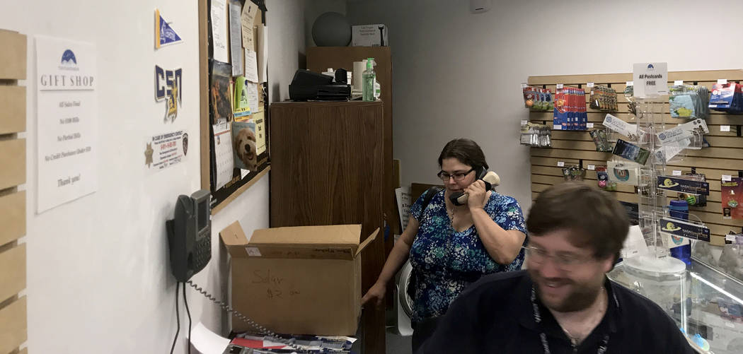 Debra Kerr, wife of Planetarium Manager Andrew Kerr, answers phone calls at the gift shop Thursday, Aug. 17, 2017, while her husband helps customers buying solar eclipse glasses. Jessie Bekker Las ...