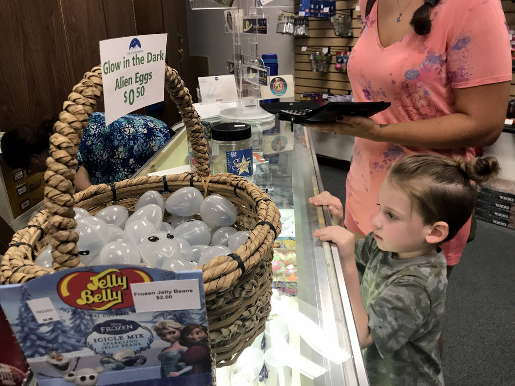 Elliott Koutz, 4, stares at the solar eclipse glasses and other astrology-themed trinkets his mom, Stephanie, is buying at the College of Southern Nevada's Planetarium store Thursday, Aug. 17, 201 ...