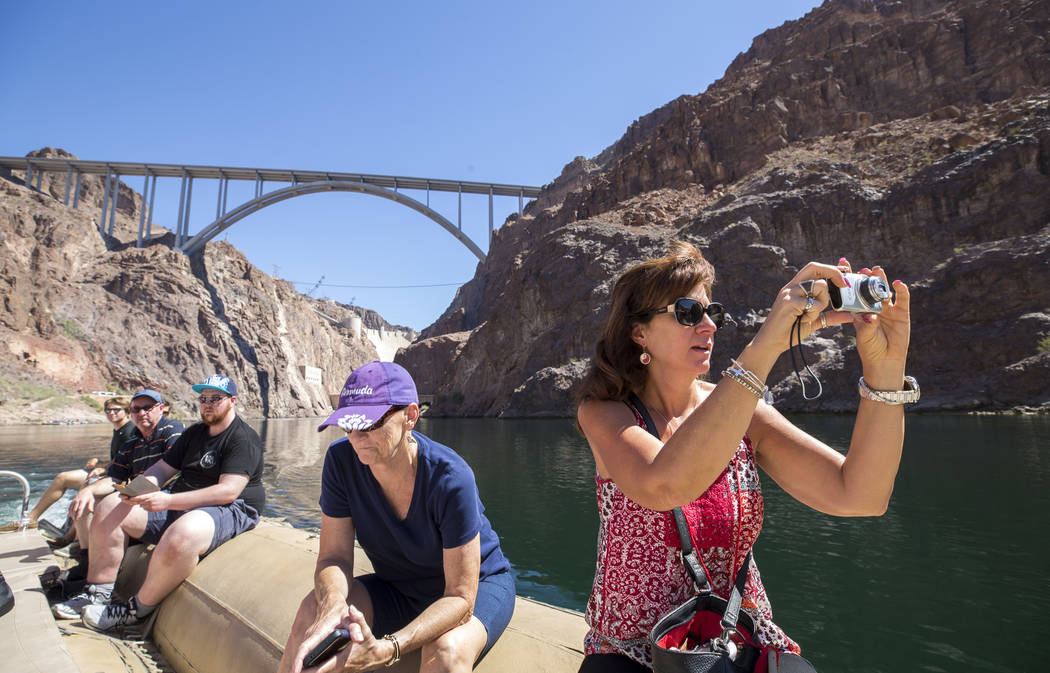 Karen Young, of Scottsdale, Ariz., takes a photo of the scenery from a Black Canyon River Adventures commercial raft during a postcard tour along the Colorado River Friday, Aug. 18, 2017, near Bou ...