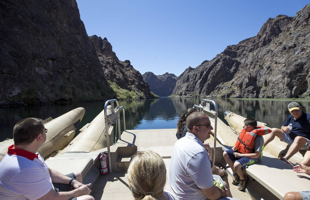 Tourists enjoy the scenery while on a Black Canyon River Adventures commercial raft during a postcard tour along the Colorado River Friday, Aug. 18, 2017, near Boulder City. The rafting outfitter  ...