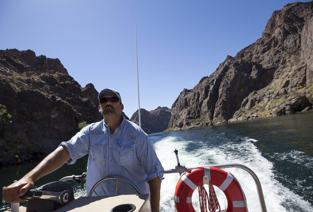 Bret Hood, a raft pilot for Black Canyon River Adventures, leads a postcard tour of Hoover Dam and bypass bridge along the Colorado River Friday, Aug. 18, 2017, near Boulder City. The rafting outf ...