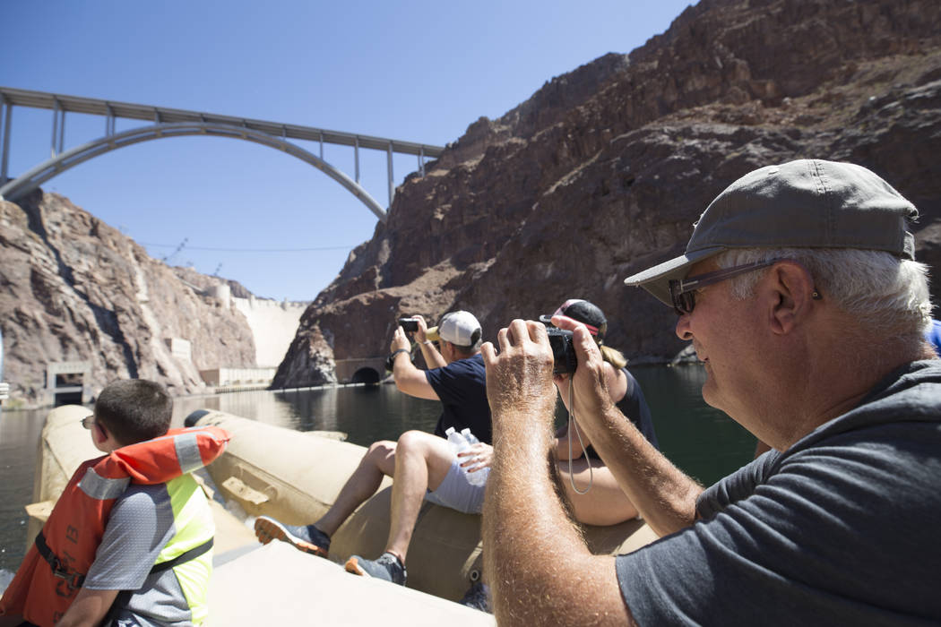 Dick Pavlick, of Baltimore, Md., takes a photo of the Hoover Dam and bypass bridge from a Black Canyon River Adventures commercial raft during a postcard tour of the Colorado River Friday, Aug. 18 ...