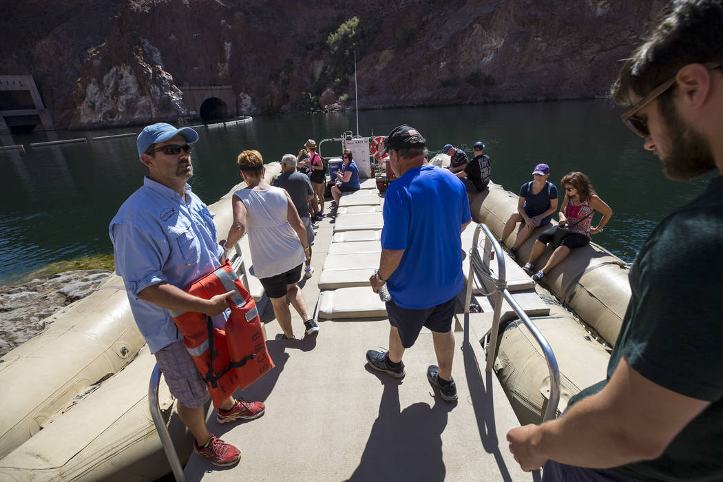 Bret Hood, a raft pilot for Black Canyon River Adventures, greets tourist as they board his commercial raft for a postcard tour of the Hoover Dam and bypass bridge along the Colorado River Friday, ...