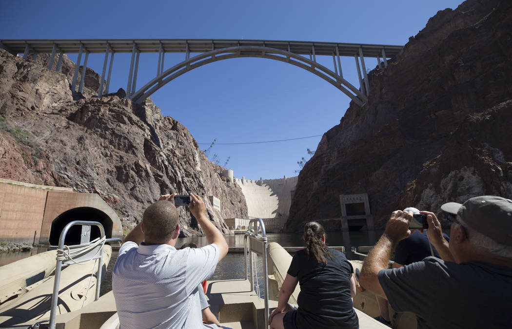 Tourists snap photos of the Hoover Dam and bypass bridge from a Black Canyon River Adventures commercial raft during a postcard tour along the Colorado River Friday, Aug. 18, 2017, near Boulder Ci ...