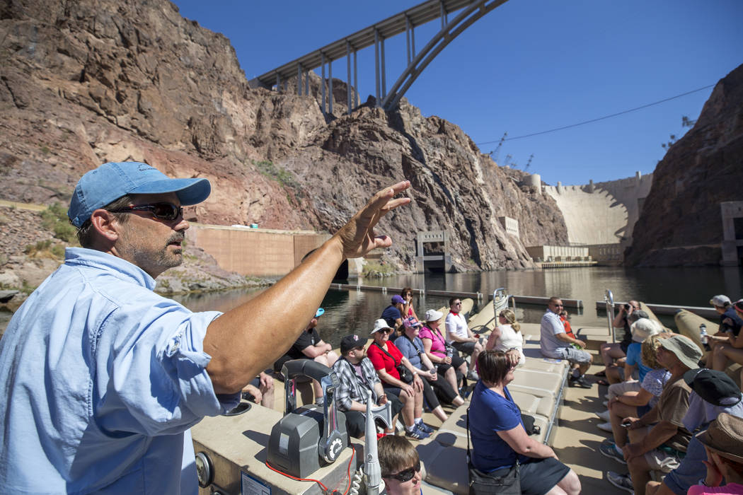 Bret Hood, a raft pilot for Black Canyon River Adventures, leads tourist on a postcard tour of Hoover Dam and bypass bridge along the Colorado River Friday, Aug. 18, 2017, near Boulder City. The r ...