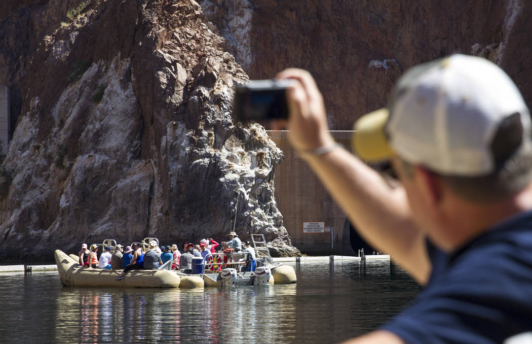 Brad Doss, of Atlanta, Ga., takes a photo of the Hoover Dam and bypass bridge from a Black Canyon River Adventures commercial raft during a postcard tour of the Colorado River Friday, Aug. 18, 201 ...