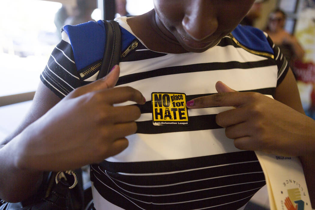A sticker is put on during a vigil for peace and unity and for Las Vegans to stand shoulder-to-shoulder in denouncing anti-Semitism, racism and bigotry  at the First African Methodist Episcopal Ch ...