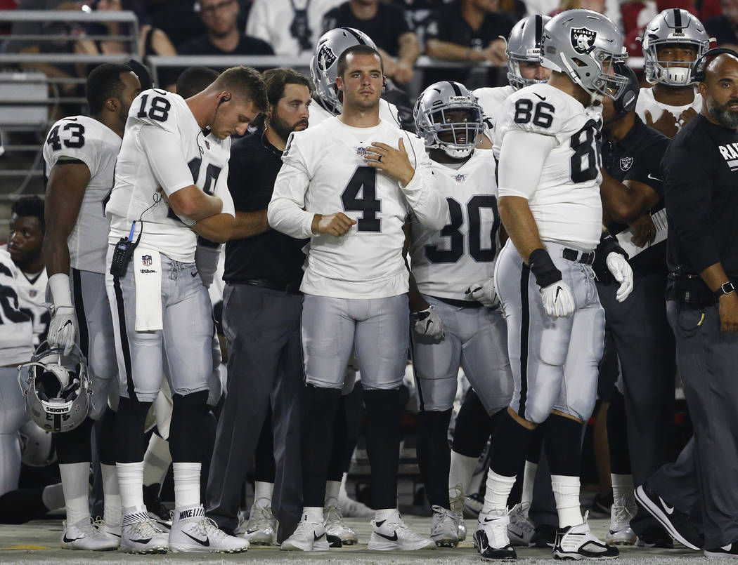 Oakland Raiders quarterback Derek Carr (4) watches from the sidelines during the first half of the team's NFL preseason football game against the Arizona Cardinals, Saturday, Aug. 12, 2017, in Gle ...