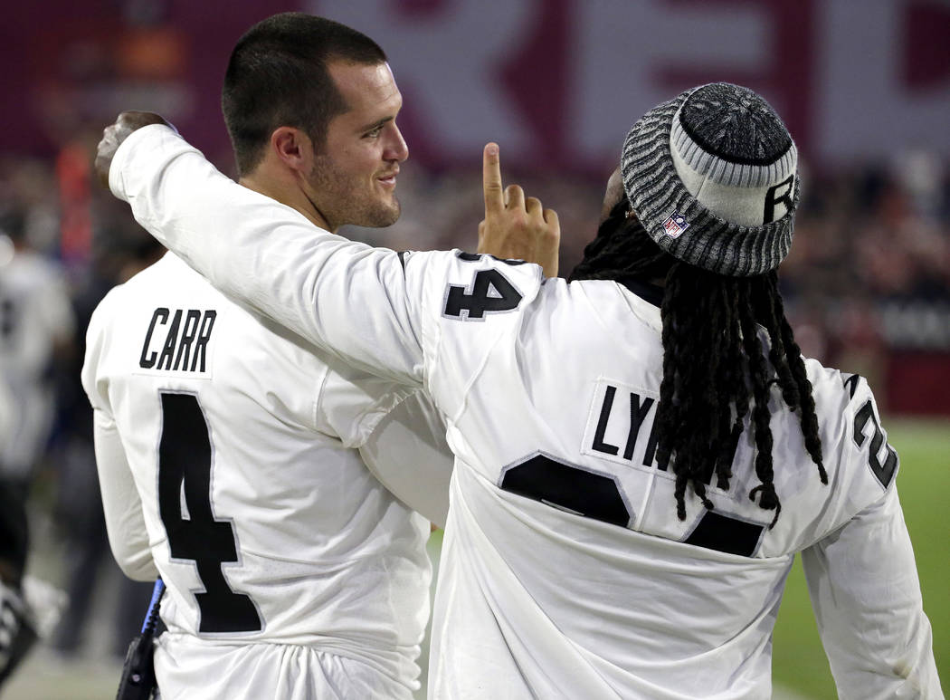 Oakland Raiders quarterback Derek Carr (4) and Marshawn Lynch talks on the sideline during the first half of an NFL preseason football game against the Arizona Cardinals, Saturday, Aug. 12, 2017,  ...