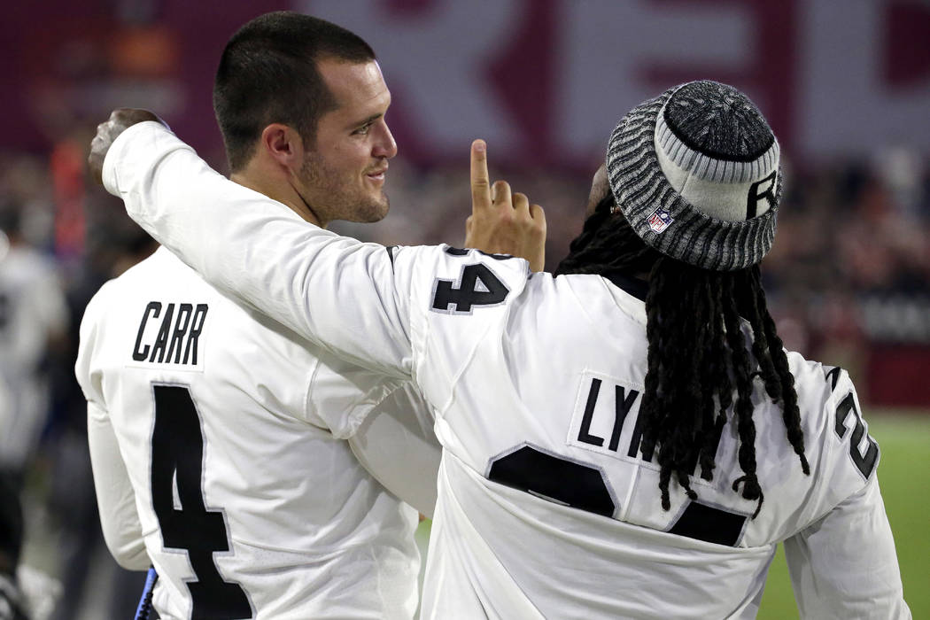Oakland Raiders quarterback Derek Carr (4) and Marshawn Lynch talk on the sideline during the first half of an NFL preseason football game against the Arizona Cardinals, Saturday, Aug. 12, 2017, i ...