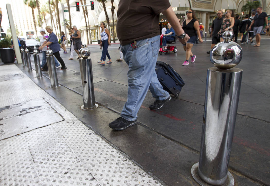 Pedestrians walk past safety bollards at the Fremont Street Experience in downtown Las Vegas on Thursday, June 8, 2017. Clark County commissioners are taking bids for the installation of hundreds  ...