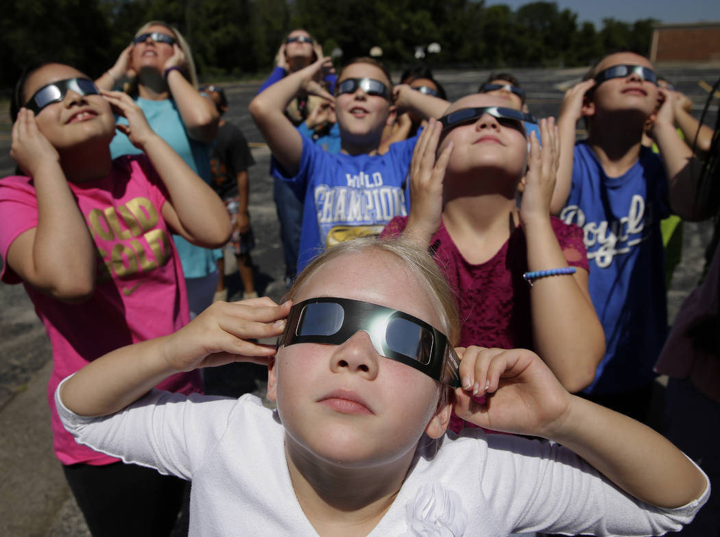 In this photo taken Friday, Aug. 18, 2017, fourth graders at Clardy Elementary School in Kansas City, Mo. practice the proper use of their eclipse glasses in anticipation of Monday's solar eclipse ...