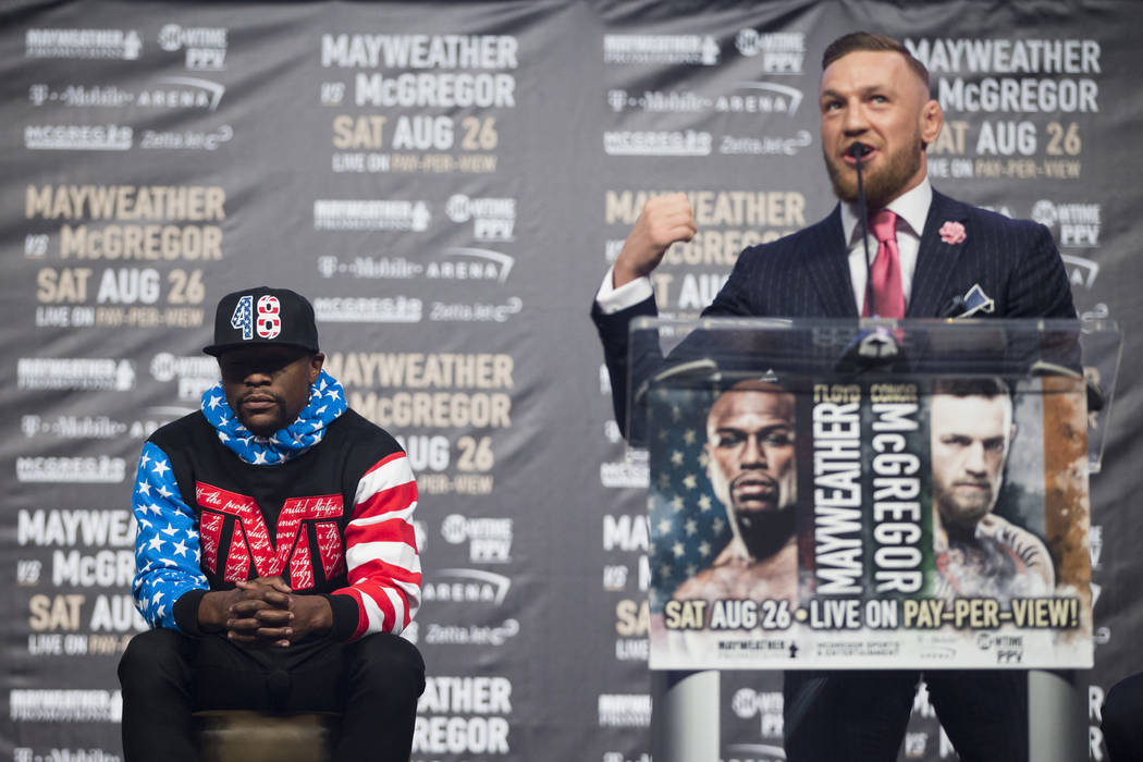 UFC fighter Conor McGregor, right, during a world tour event stop to promote his upcoming fight against Boxer Floyd Mayweather Jr., left, at Staples Center in Los Angeles, Calif., on Tuesday, July ...