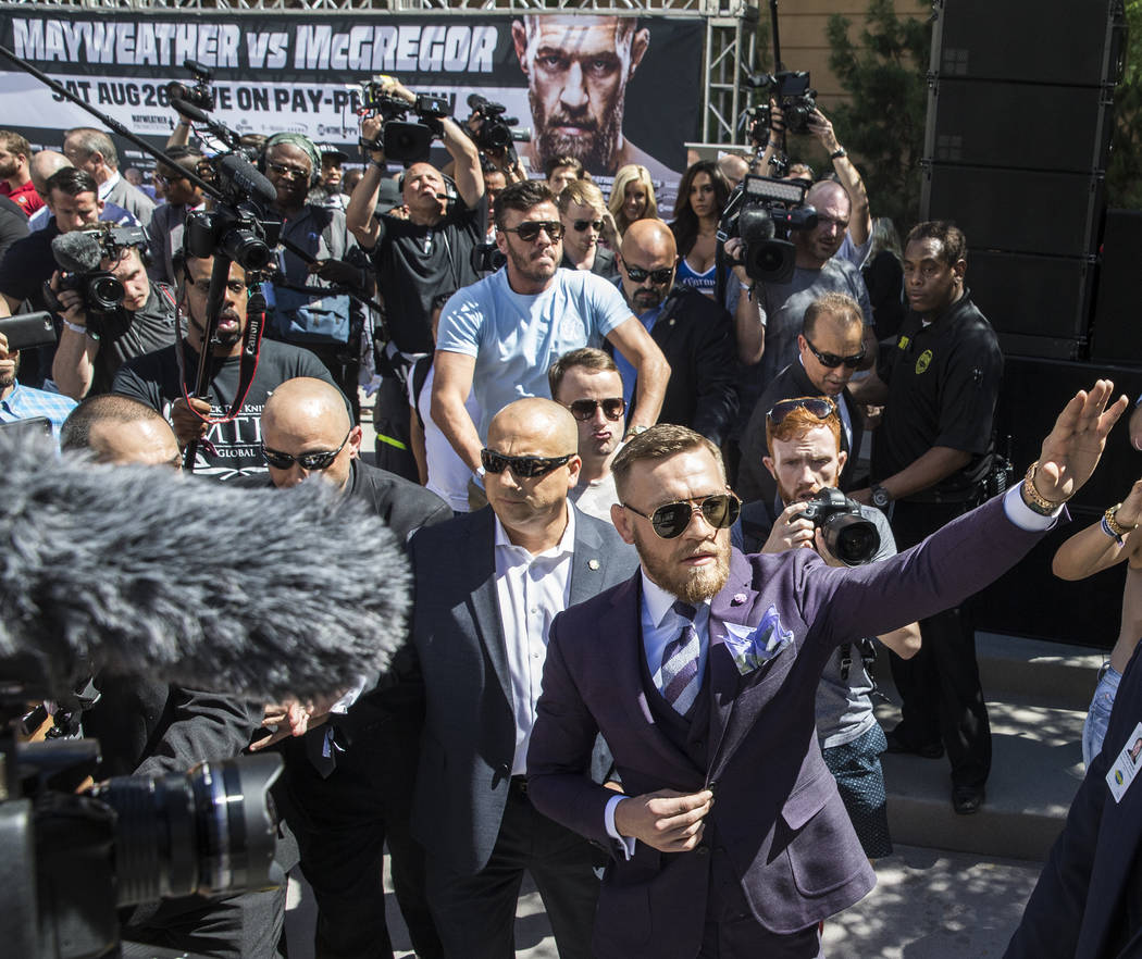 Conor McGregor, right, waves to fans during his arrival at Toshiba Plaza outside T-Mobile Arena in advance of his Saturday night fight with Floyd Mayweather Jr. Photo taken on Tuesday, Aug 22, 201 ...