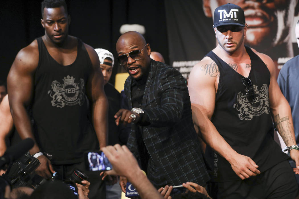 Floyd Mayweather Jr., center, exchanges words with a member in the audience during the final press conference ahead of their fight, slated for Aug. 26 at the T-Mobile Arena, at the Ka Theatre at t ...