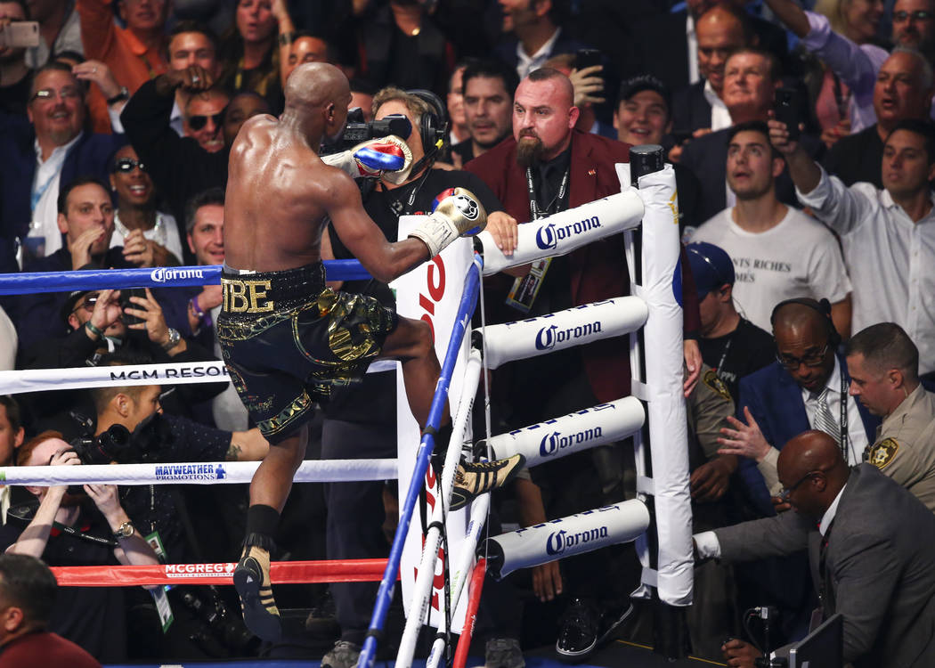 Floyd Mayweather Jr. jumps onto the ropes after defeating Conor McGregor in their super welterweight fight at T-Mobile Arena, Saturday, Aug. 26, 2017, in Las Vegas. Mayweather won via 10th round t ...