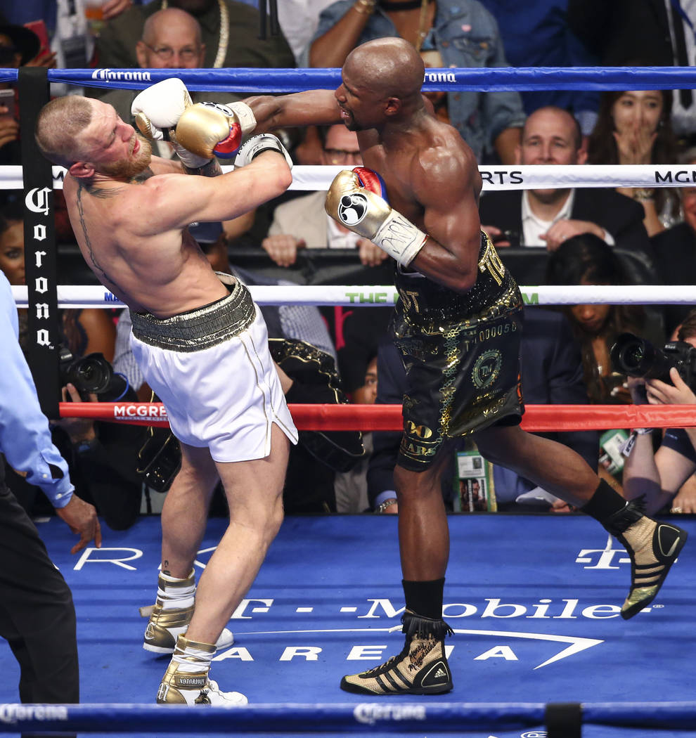 Floyd Mayweather Jr., right, delivers the final blows to Conor McGregor in their super welterweight fight at T-Mobile Arena, Saturday, Aug. 26, 2017, in Las Vegas. Mayweather won via 10th round te ...