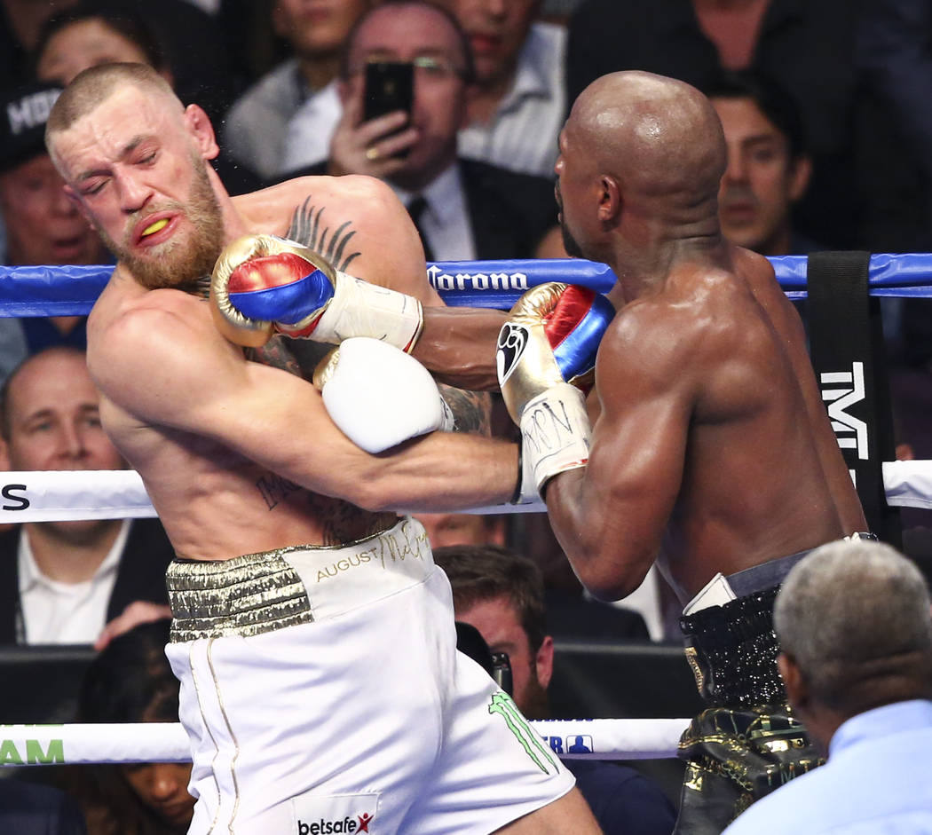 Conor McGregor, left, fights Floyd Mayweather Jr. in their super welterweight fight at T-Mobile Arena, Saturday, Aug. 26, 2017, in Las Vegas. Mayweather won via 10th round technical knockout. Chas ...
