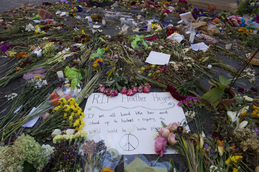 A notes and flowers form a memorial in Charlottesville, Va., on Friday, Aug. 18, 2017 at the site where Heather Heyer was killed. Heyer was struck by a car while protesting a white nationalist ral ...