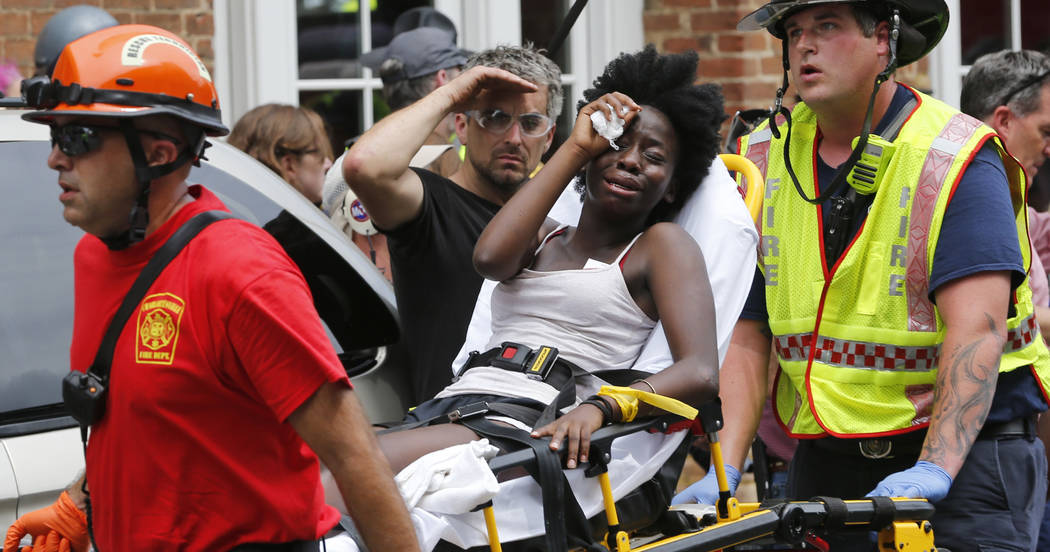Rescue personnel help an injured woman after a car ran into a large group of protesters after an white nationalist rally in Charlottesville, Va., Saturday, Aug. 12, 2017.  The nationalists were ho ...