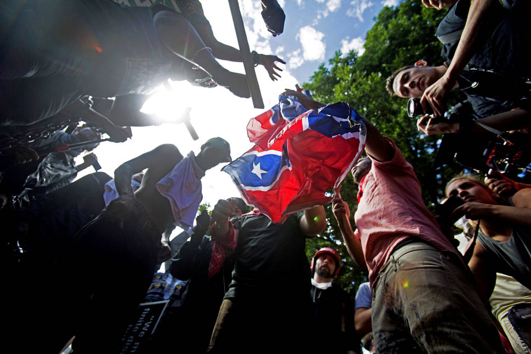 FILE - In this Aug. 12, 2017 file photo, counter-protesters tear a Confederate flag during a white nationalist rally in Charlottesville, Va. The deadly white nationalist demonstration in Virginia  ...