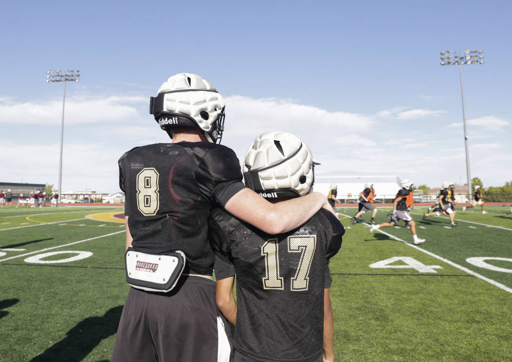 Faith Lutheran wide receiver Elija Kothe (8), left, puts his arm around wide receiver and corner back Brian Dunn's (17) shoulder while watching a play during practice at Faith Lutheran High School ...