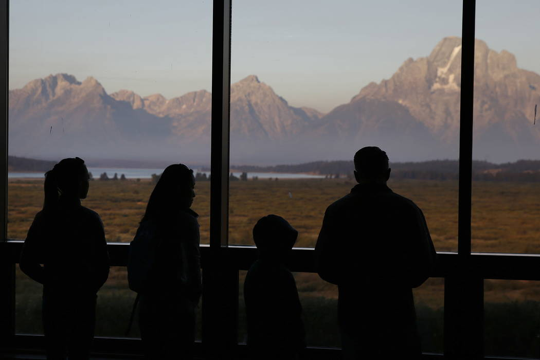 Visitors watch the sun illuminate the Grand Tetons at the Jackson Lake Lodge, in Grand Teton National Park, north of Jackson Hole, Wyo., in 2016. (AP Photo/Brennan Linsley, File)