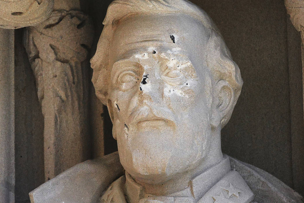 The defaced Gen. Robert E. Lee statue stands at the Duke Chapel on Thursday, Aug. 17 2017, in Durham, N.C. (Bernard Thomas/The Herald-Sun via AP)