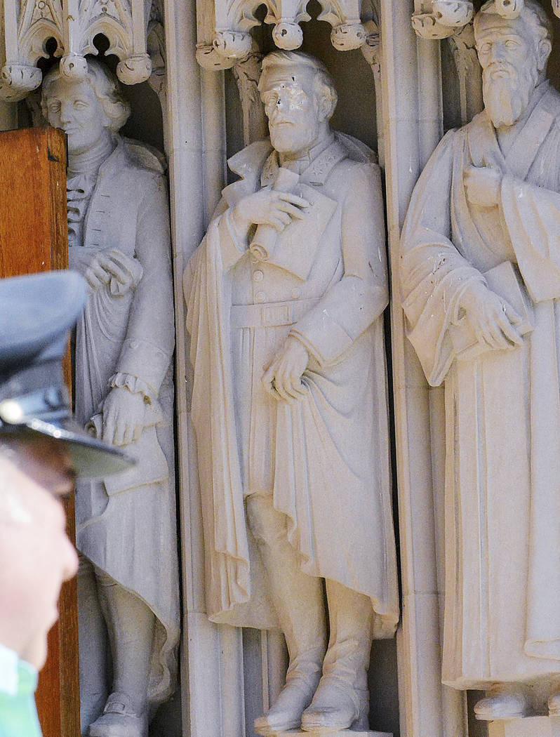 The defaced Gen. Robert E. Lee statue, center, stands at the Duke Chapel in Durham, N.C. Duke  Duke University removed a statue of Gen. Robert E. Lee early Saturday, Aug. 19, days after it was van ...