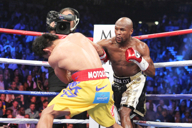Floyd Mayweather Jr. hits Manny Pacquiao with a right during their welterweight unification boxing match at the MGM Grand Garden Arena in Las Vegas on Saturday, May 2, 2015. (Sam Morris/Las Vegas  ...
