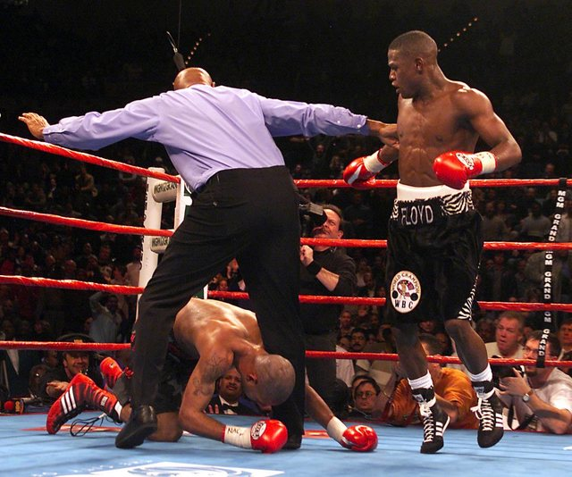 Diego Corrales gets tied up in the legs of referee Richard Steele after getting knocked down by Floyd Mayweather, right, in the seventh round of their WBC Super Featherweight Championship bout at  ...
