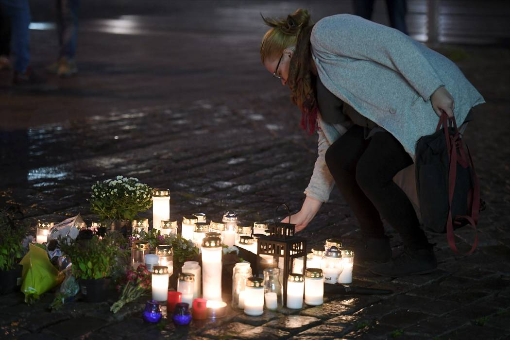 A woman places a memorial candle at the Market Square for the victims of Friday's stabbings in Turku, Finland, on Friday evening, Aug. 18, 2017. Several people were stabbed on the Market Square on ...