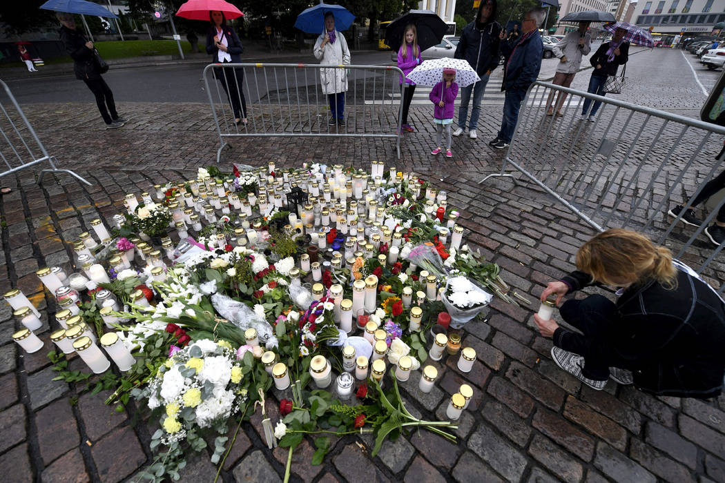 A woman places a candle by floral tributes for the victims of an attack at Turku Market Square on Friday, in Turku, Finland, Saturday, Aug. 19, 2017.  A suspect detained for allegedly stabbing two ...