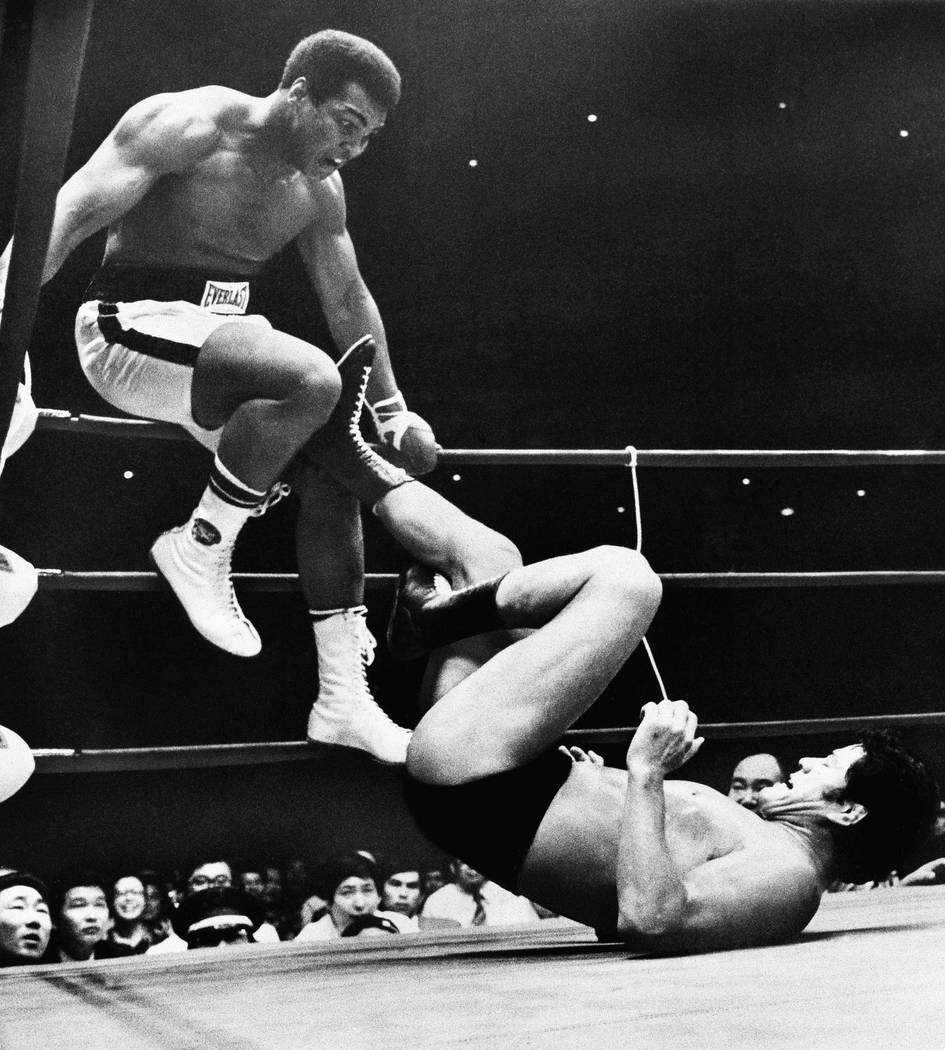 In this July 26, 1976, file photo, world heavyweight boxing champion Muhammad Ali is shown trying to evade kicks by wrestler Antonio Inoki during their 15-round World Martial Arts match, in Tokyo. ...