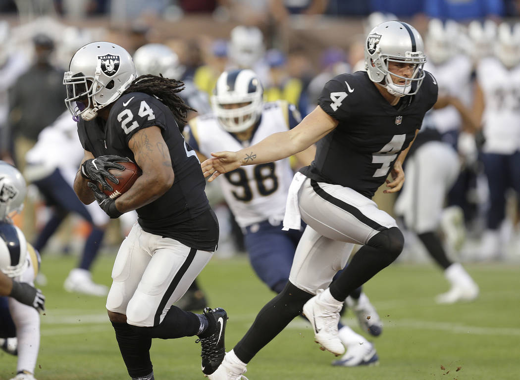 Oakland Raiders running back Marshawn Lynch (24) takes a handoff from quarterback Derek Carr (4) during the first half of an NFL preseason football game against the Los Angeles Rams in Oakland, Sa ...