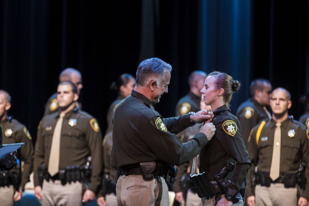 Sheriff Joseph Lombardo puts a badge on officer Laura Van Dyke's uniform during the Metropolitan Police Department graduation ceremony at The Orleans in Las Vegas on Monday, Aug. 21, 2017. Elizabe ...