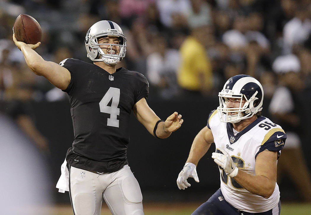Oakland Raiders quarterback Derek Carr (4) passes as Los Angeles Rams defensive end Matt Longacre applies pressure during the first half of an NFL preseason football game in Oakland, Saturday, Aug ...