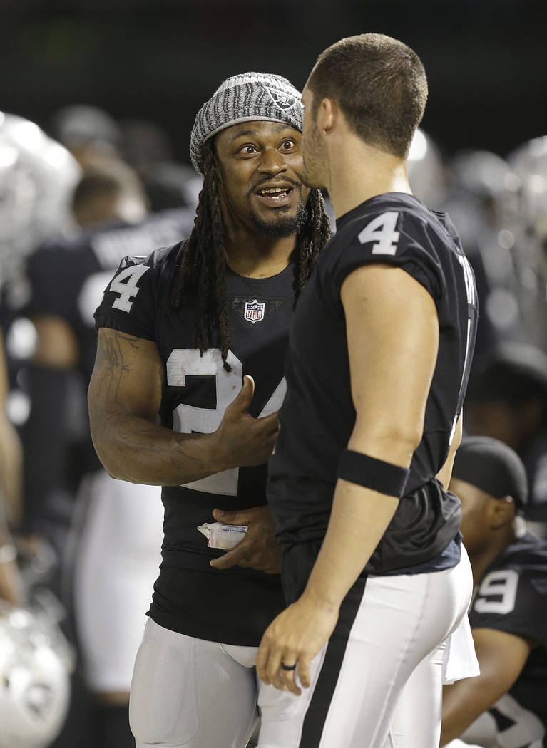 Oakland Raiders running back Marshawn Lynch (24) talks on the sideline with quarterback Derek Carr during the first half of an NFL preseason football game against the Los Angeles Rams in Oakland,  ...