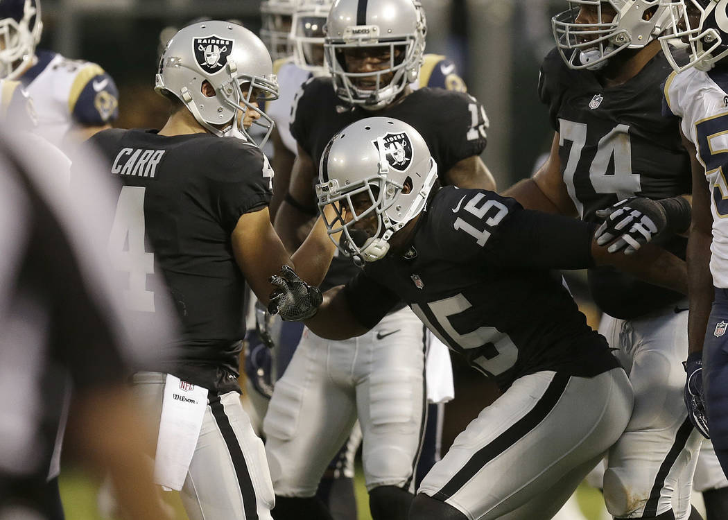 Oakland Raiders quarterback Derek Carr (4) and wide receiver Michael Crabtree (15) celebrate after connecting on a touchdown pass against the Los Angeles Rams during the first half of an NFL prese ...