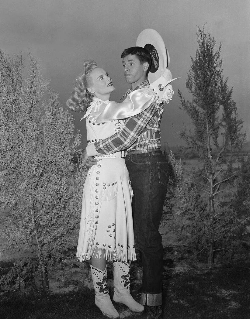 In a spot most men would envy, Jerry Lewis appears quite at a loss in the face of amorous advances on the part of actress Marie Wilson during filming on location on April 11, 1950, at Las Vegas. (AP)