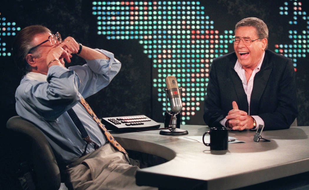 """Talk show host Larry King wipes his eyes after laughing at a joke by comedy legend Jerry Lewis Aug. 26, 1999, on the set of """"Larry King Live"""" at CNN Studios in the Hollywood section of Los Angeles ..."""