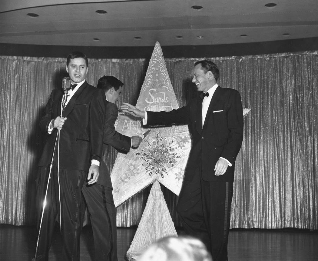 Jerry Lewis, left, and Frank Sinatra, right, joke as Danny Thomas cuts the huge star-shaped birthday cake at a party to celebrate the fourth anniversary of the Sands Hotel in Las Vegas, Nev., Dec. ...