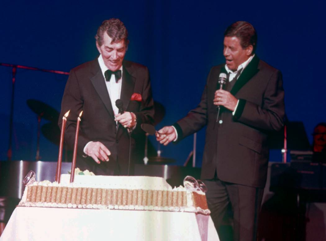 Dean Martin, left, laughs after former partner Jerry Lewis, right, presented the famed entertainer with a giant cake in honor of his 72nd birthday at Bally's in Las Vegas June 8, 1989. (File/AP)