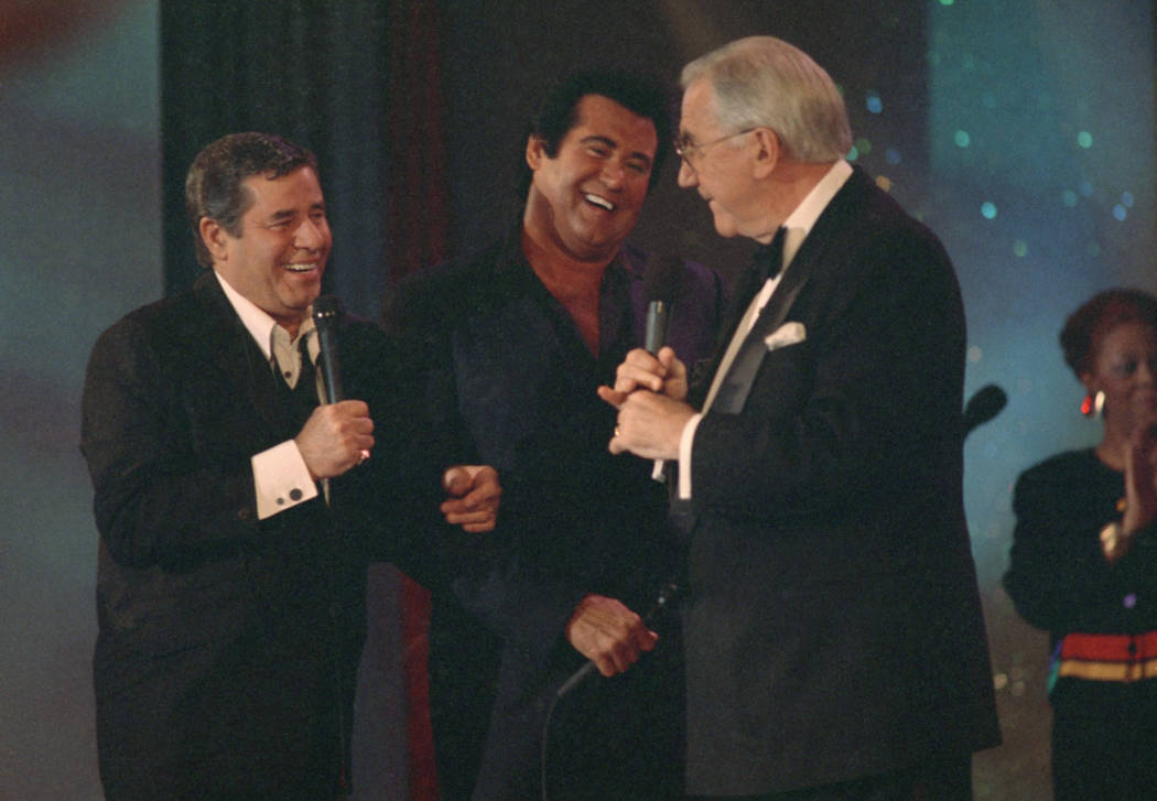 Jerry Lewis, left, shares a laugh with Wayne Newton, center, and Ed McMahon after seeing the final total of donations to the Muscular Dystrophy Association Telethon, Monday, Sept. 8, 1992, in Las  ...