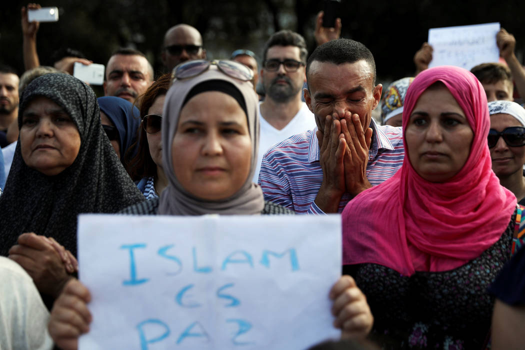 Members of the Muslim community observe a minute of silence during a gathering to denounce terrorism near the area where a van crashed into pedestrians at Las Ramblas in Barcelona, Spain, August 2 ...